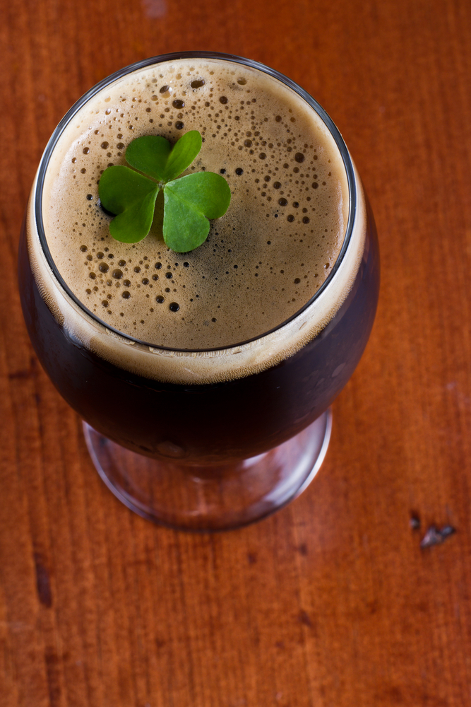 Glass of dark beer with foam and a 4 leaf clover on top against dark oak wood background