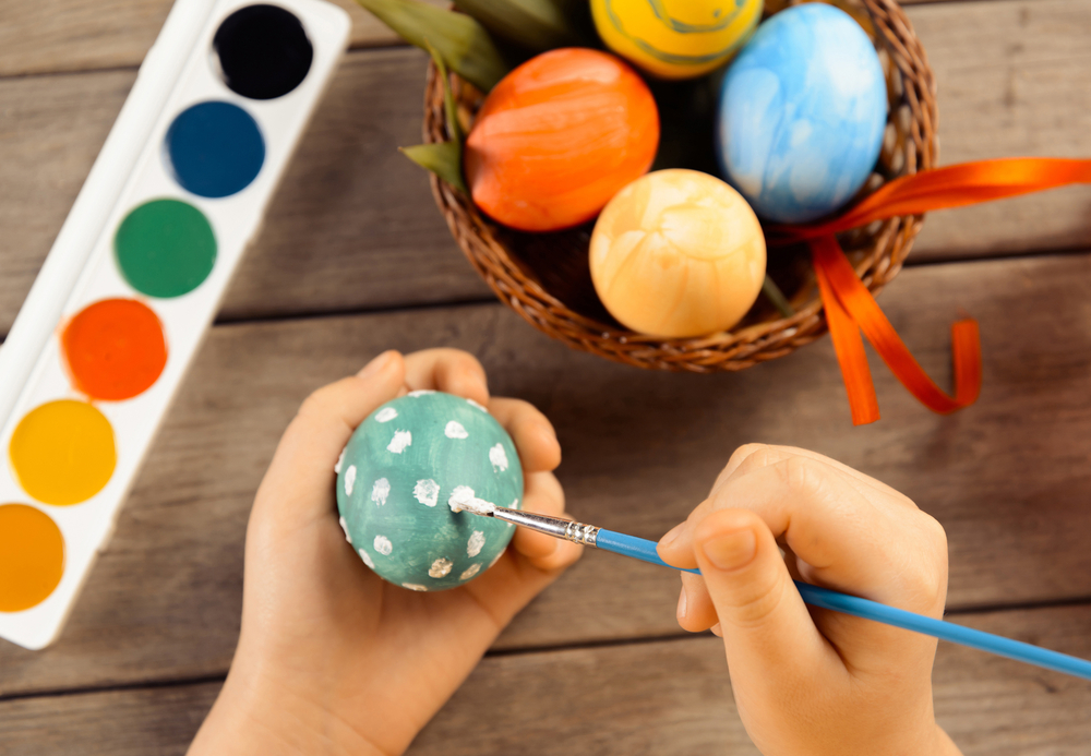 Child painting Easter eggs with brush, paint and Easter eggs in basket in background on wooden table