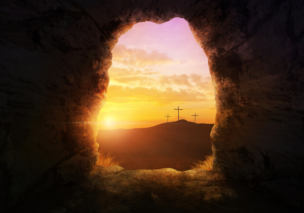 Empty tomb of resurrected Jesus open to a view of a sunrise and three crosses on a hill