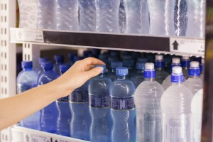 woman choosing blue bottle of water in store cooler among the bottled water options