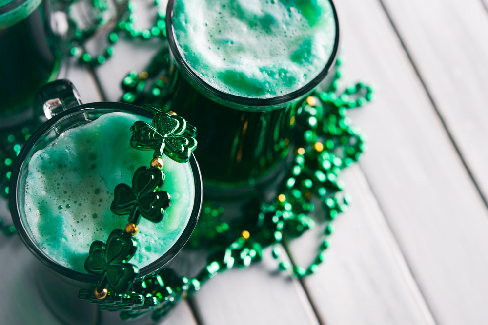 2 green bears on left with green foam, green beads with shamrocks strewn over and beside glasses, against light wood background