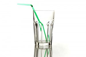 Clear, empty glass with green straw inside glass on white background