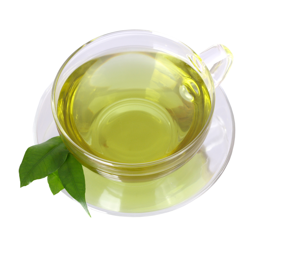 Cup of green tea in clear cup and saucer with green leaves sitting on edge of saucer on white background
