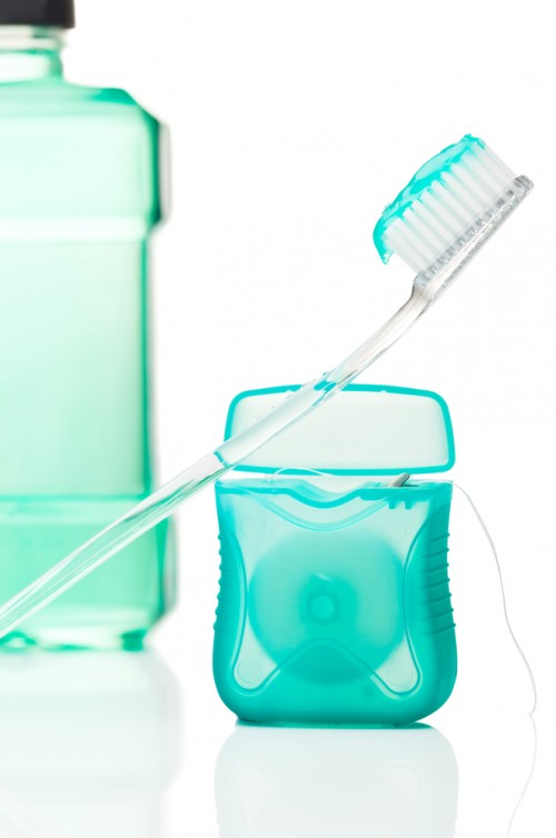 Dental care products including toothbrush with toothpaste leaning on unrolled floss with mouthwash in back left corner, against white background