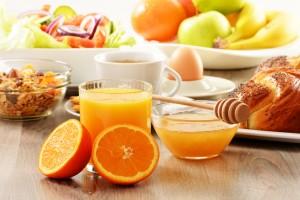 Table full of breakfast food oranges orange juice fruit coffee boiled egg croissant nuts
