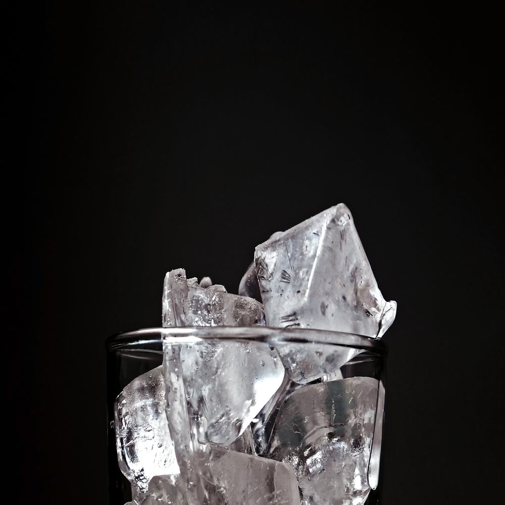 Top of clear glass full of ice stacked up past rim on black background