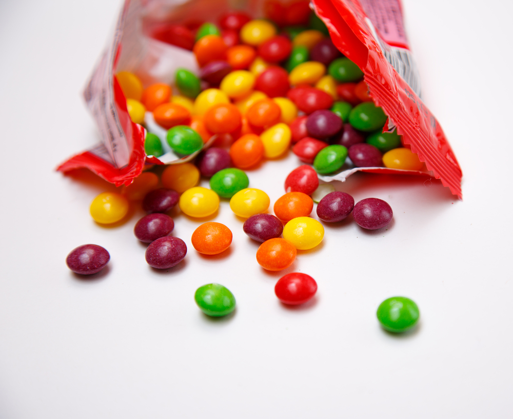 Open package of skittles on white background