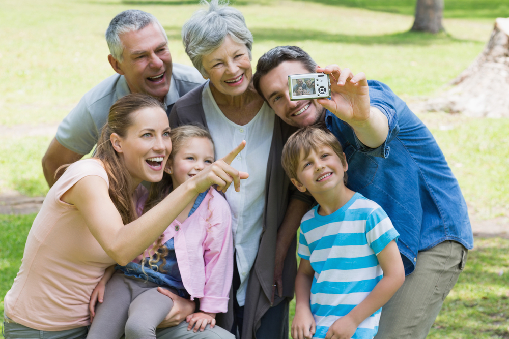 Man taking a picture with his wife, kids, and parents at a park on a sunny day