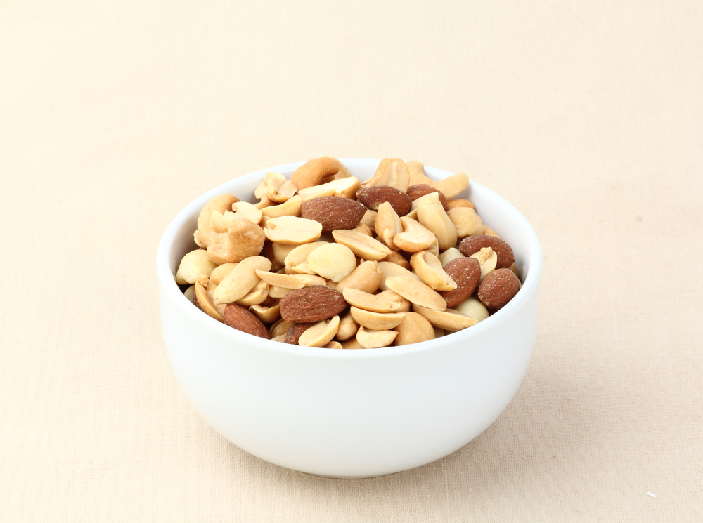 White cup of nuts (almonds, peanuts, macadamia) on light background