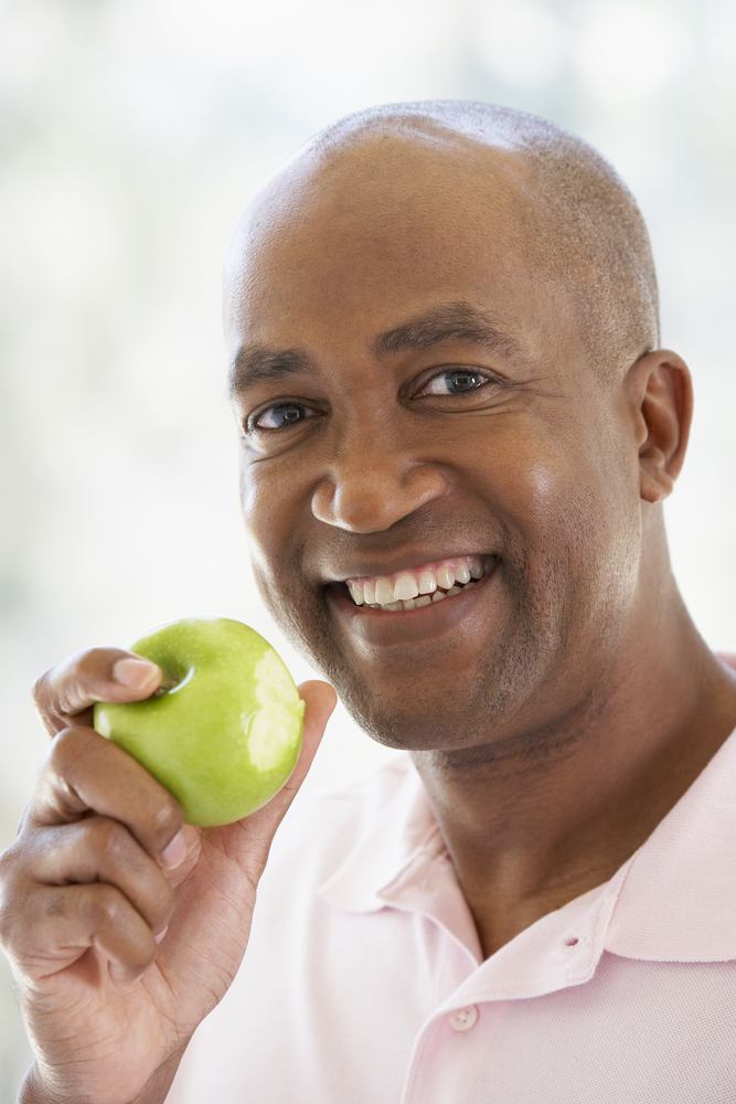 Man with beautiful teeth smiling at camera holding a green apple with a chunk already eaten