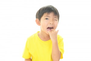 Little boy in yellow shirt pointing inside his mouth to a painful tooth that has a cavity