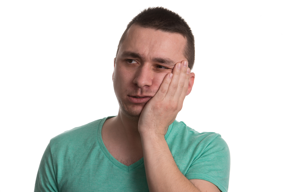 Man in green shirt with toothache holding side of face