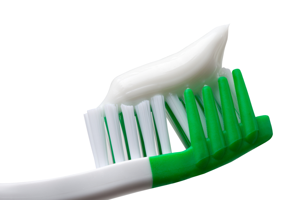 Green and white toothbrush with white toothpaste sitting on bristles