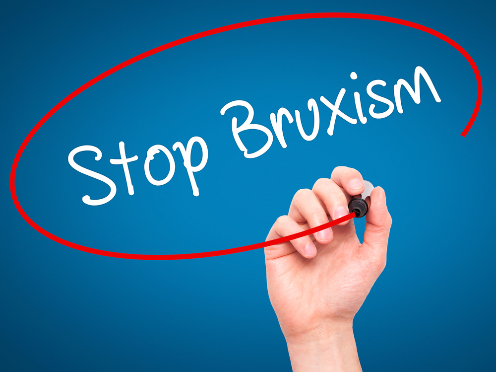 "Person circling the word ""Stop Bruxism"" with red marker on blue background"