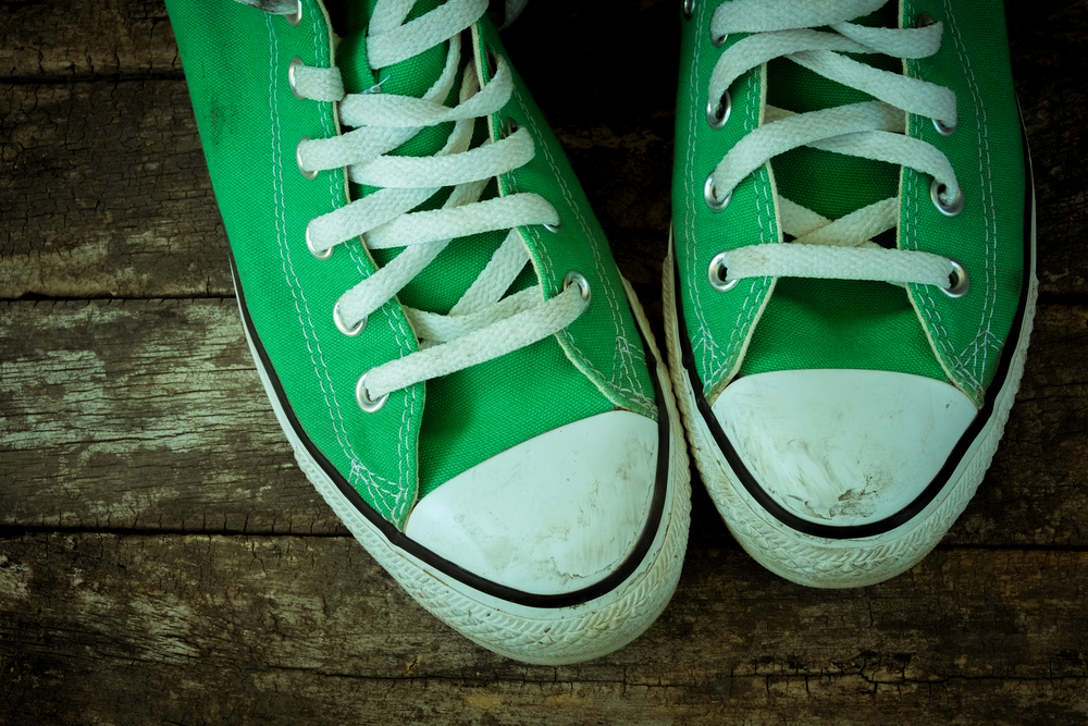 Dirty pair of green high top sneakers on wood plank background