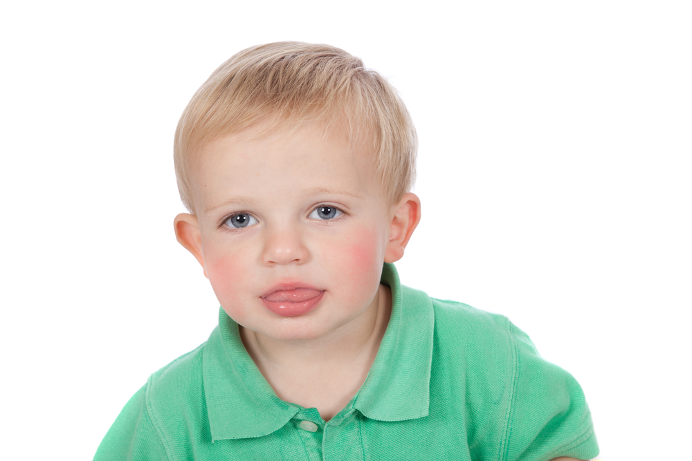 Little toddler boy with tongue between lips