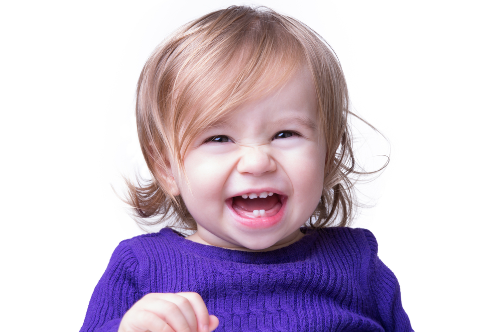 Adorable baby toddler girl with baby teeth laughing