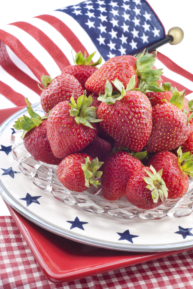 Bowl of strawberries on glass dish with blue stars and American flag in background