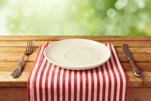 Empty white plate on red and white striped table mat with fork and knife on wood picnic table with trees in background on a beautiful summer day
