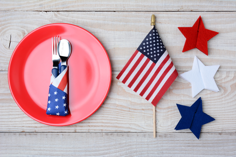 Patriotic table set up red plate with silverware wrapped in red white and blue napkin American flag and red white and blue starts on wooden table