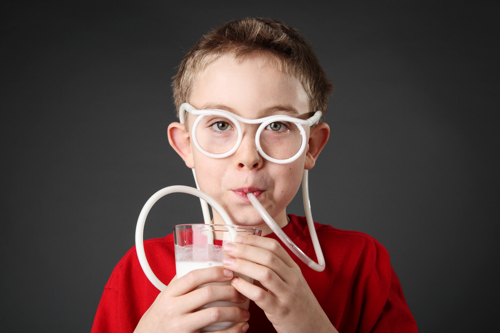 Boy drinking glass of milk through silly straw glasses