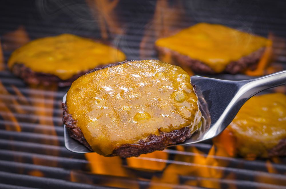 Spatula holding cheeseburger of grill with flames cooking 3 other patties with cheese
