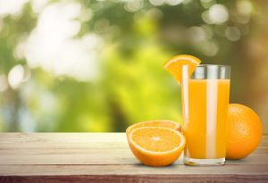 Glass of orange juice with orange slice on rim on picnic table with slived orange and full orange next to the glass on a sunny day