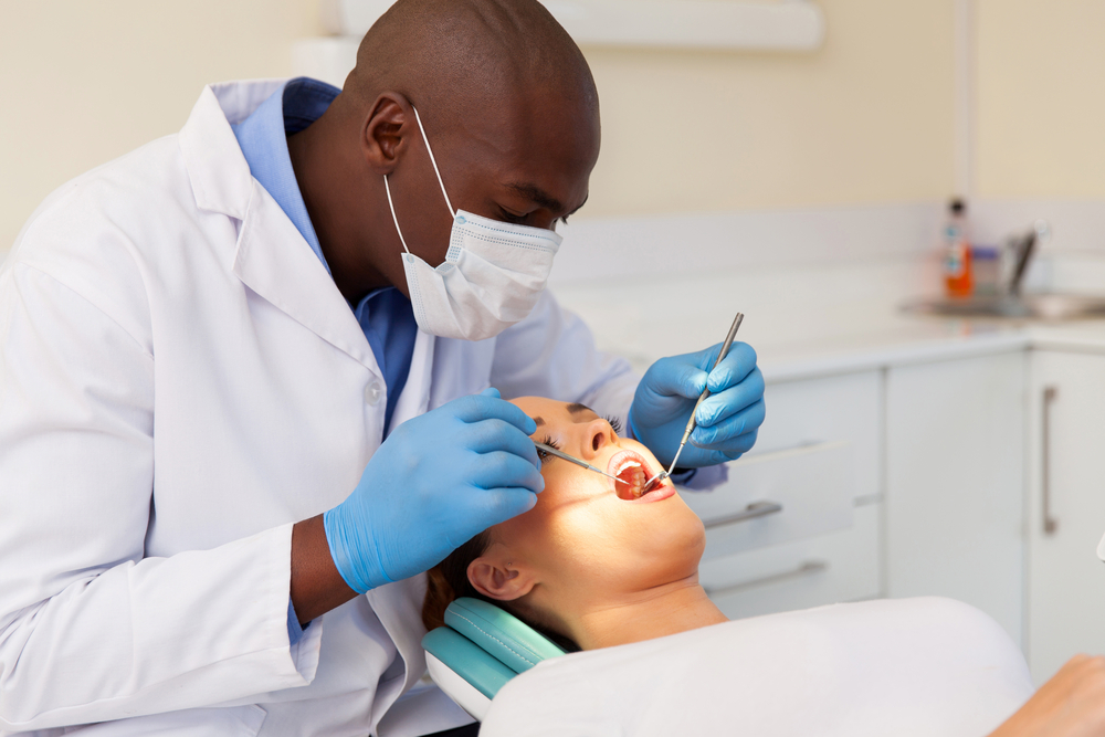 Dentist man examining woman patient's mouth with dental tools