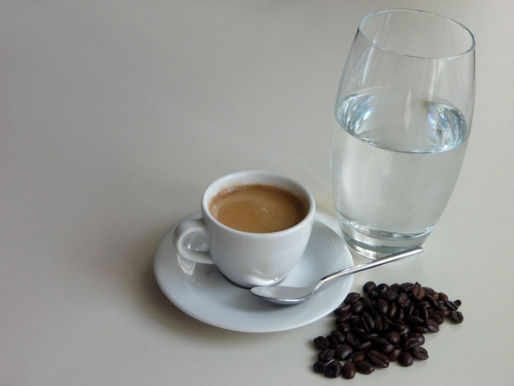 Cup of coffee on saucer with spoon next to coffee beans and glass of water