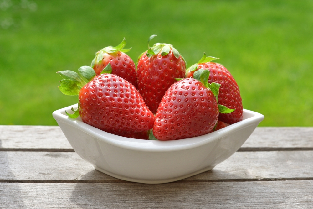 Bowl of strawberries on picnic table with green grass in background