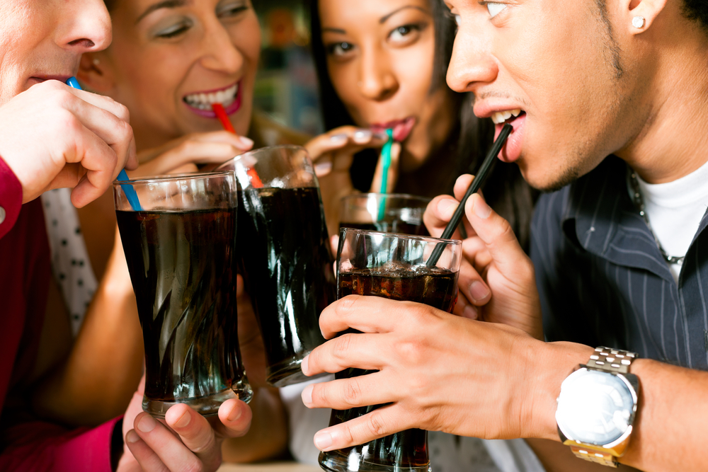 Group of 4 friends drinking glasses of soda through straws