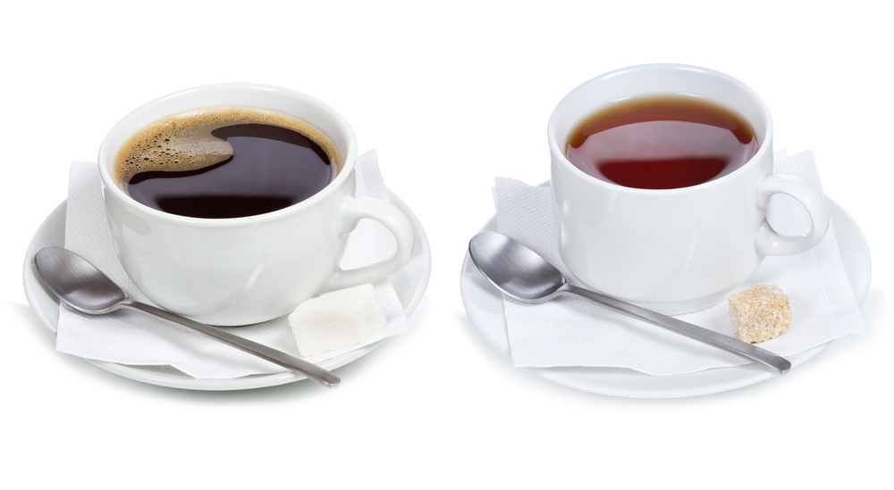 Cup of coffee on saucer with spoon and packet of sugar and cup of tea on saucer with spoon and sugar cube
