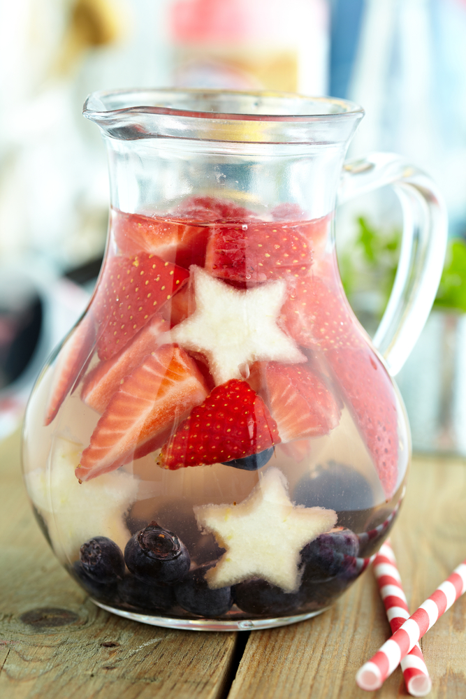 Glass pitcher of water with strawberries pineapple stars and blueberries patriotic