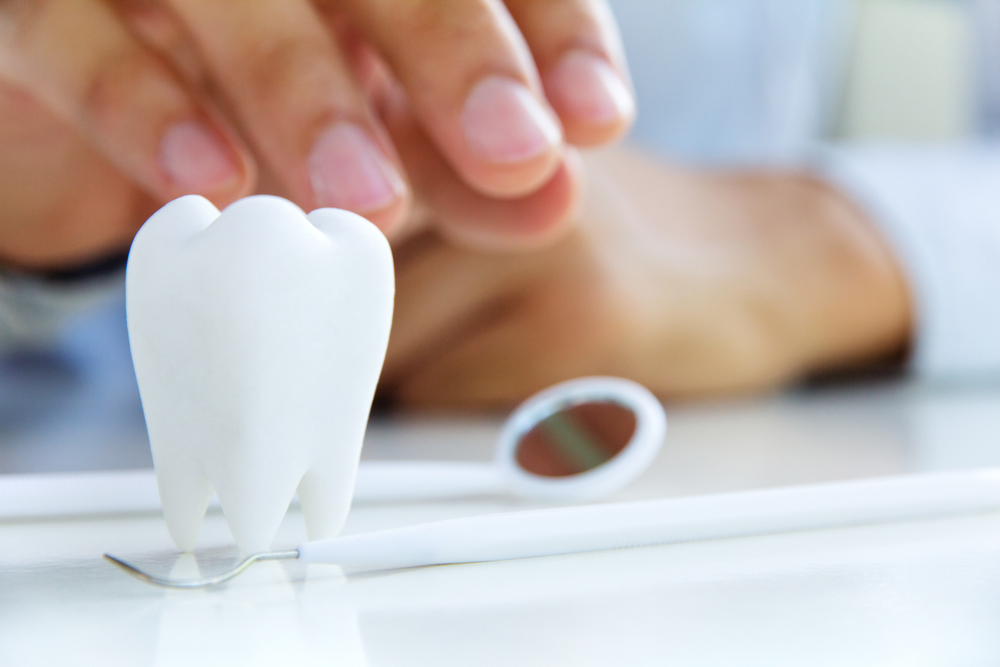 Dentist reaching for dental mirror behind model tooth and dental tartar scraper on table