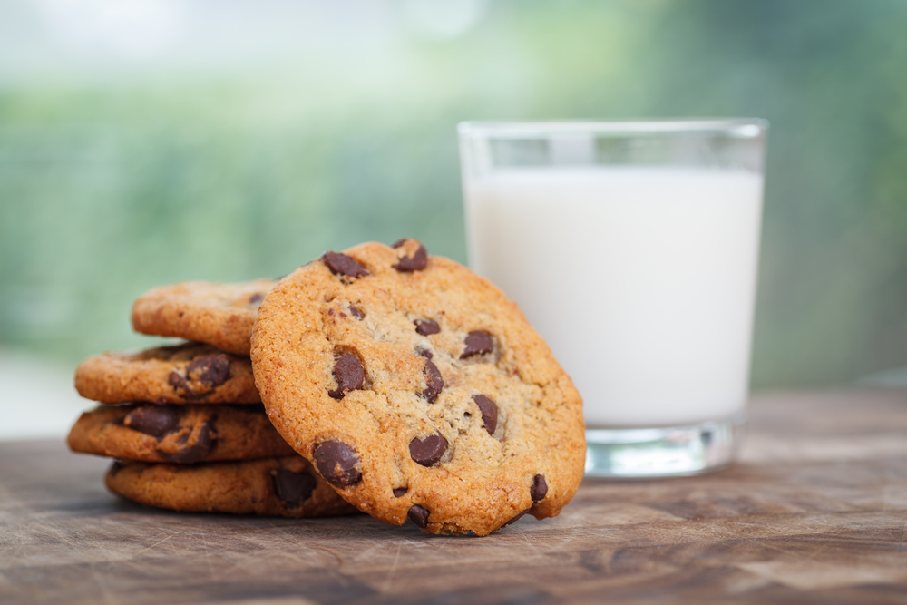 5 chocolate chip cookies stacked next to a glass of milk on a wood table