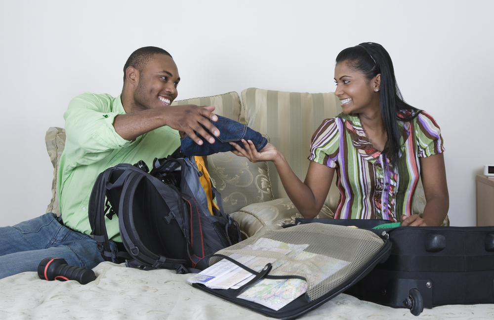 Husband and wife on bed with backpack and suitcase packing for a trip