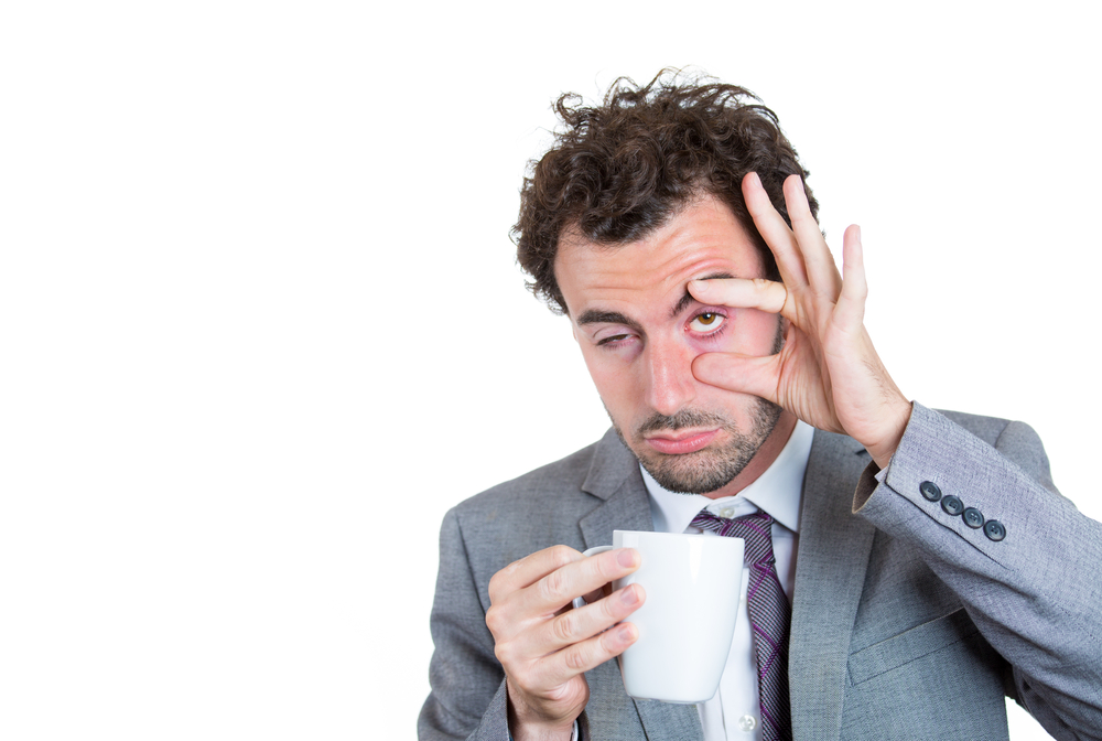 Tired man holding a cup of coffee with one hand and trying to hold his eye open with the other hand