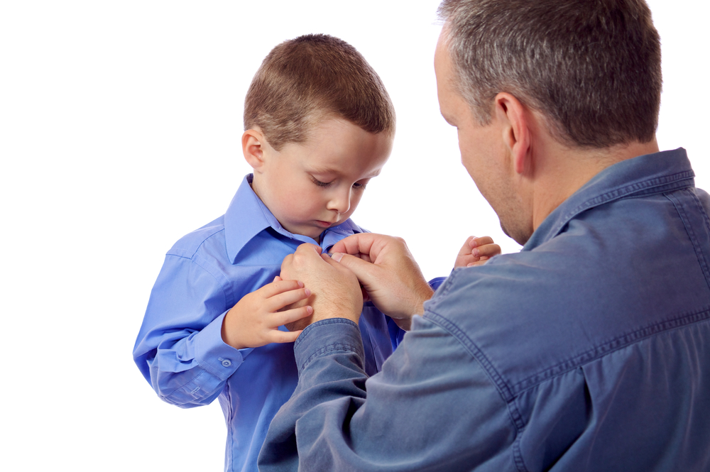 Father helping young toddler son button his shirt