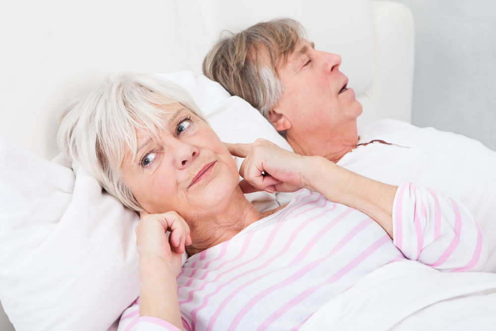 Wife holding ears in bed next to her husband who is snoring