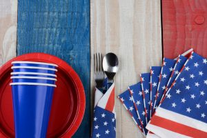 Patriotic plates cups napkins on red white and blue picnic table for 4th of July