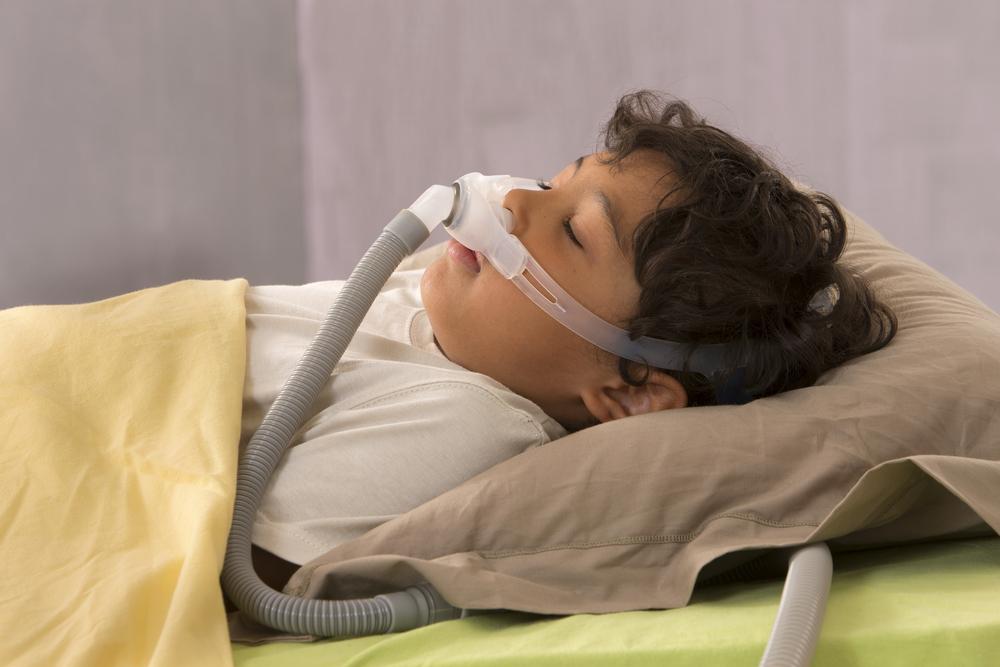Little boy sleeping with a CPAP mask on his face to treat sleep apnea