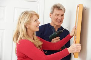Husband with drill helping wife hang a picture on the wall