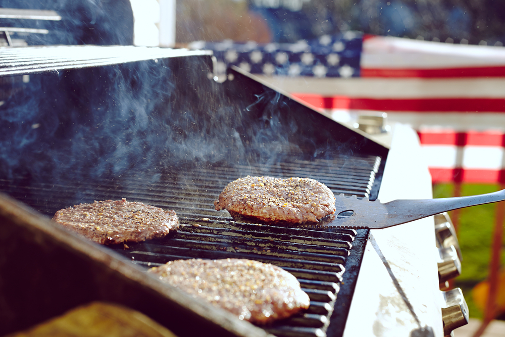 Spatula holding burger patty above grill with other paties with American flag in background