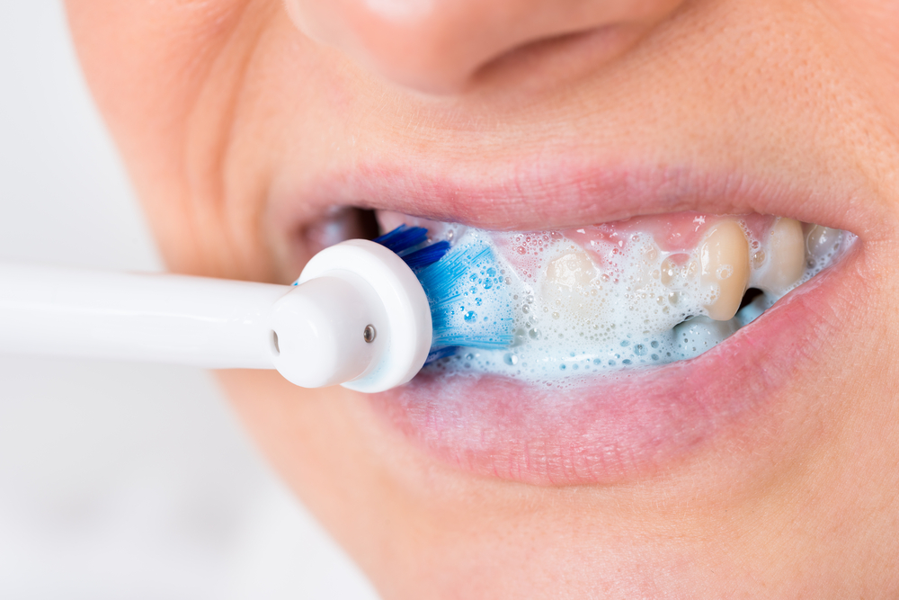 Close up of woman brushing her teeth with electric toothbrush and toothpaste
