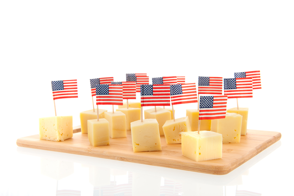 Cheese cubes with American flags on toothpicks on wood cutting board
