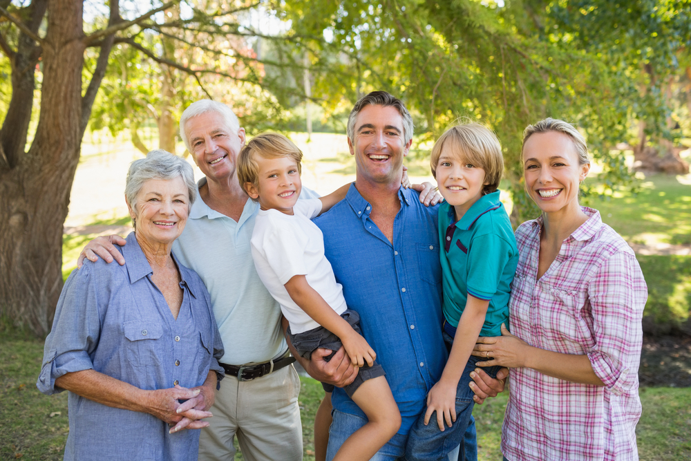 Family smiling in park under beautiful tree in summer