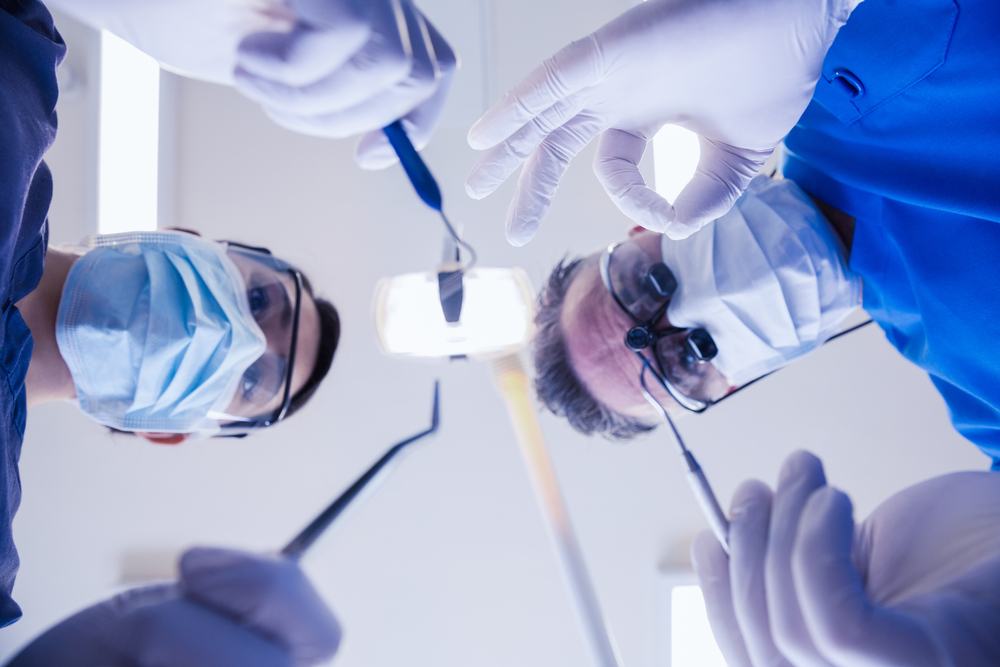 Dentist and dental assistant above patient with dental tools and dentist making okay sign