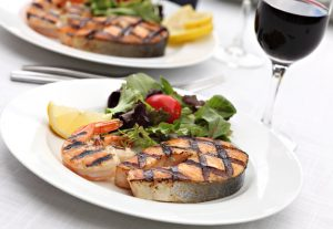 Grilled salmon with lemon and salad with tomatoes on plate with glass of wine