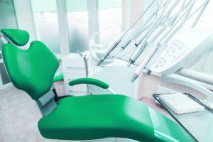 Green dental examination chair with dental tools