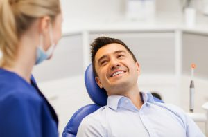 Smiling male patient in dental chair talking with female dental hygienist